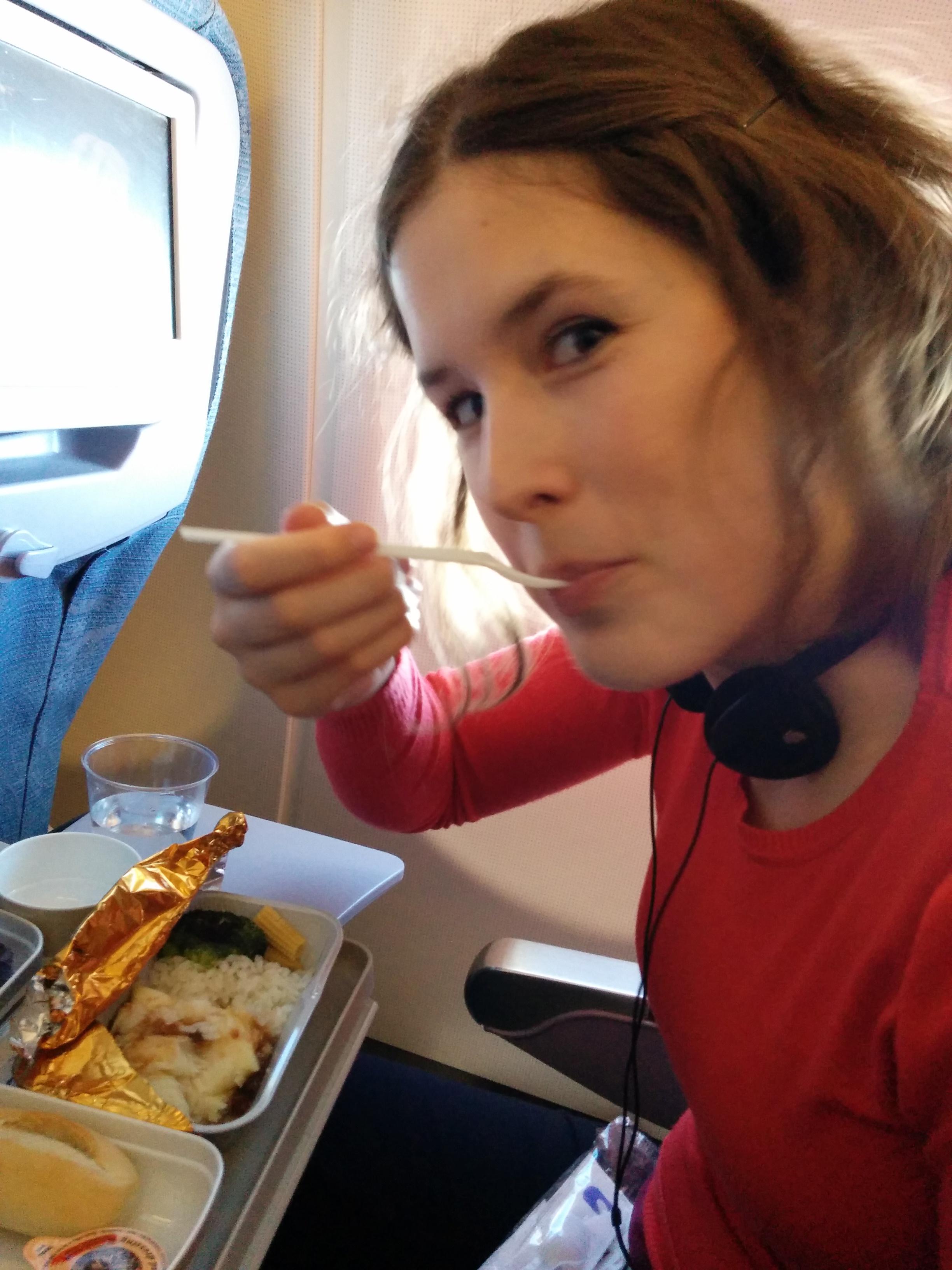 Veronika eating airplane food.
