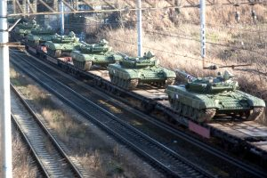 Tanks on the train being transporter through the middle of the city.