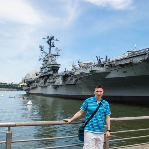 Me in front of aircraft carrier