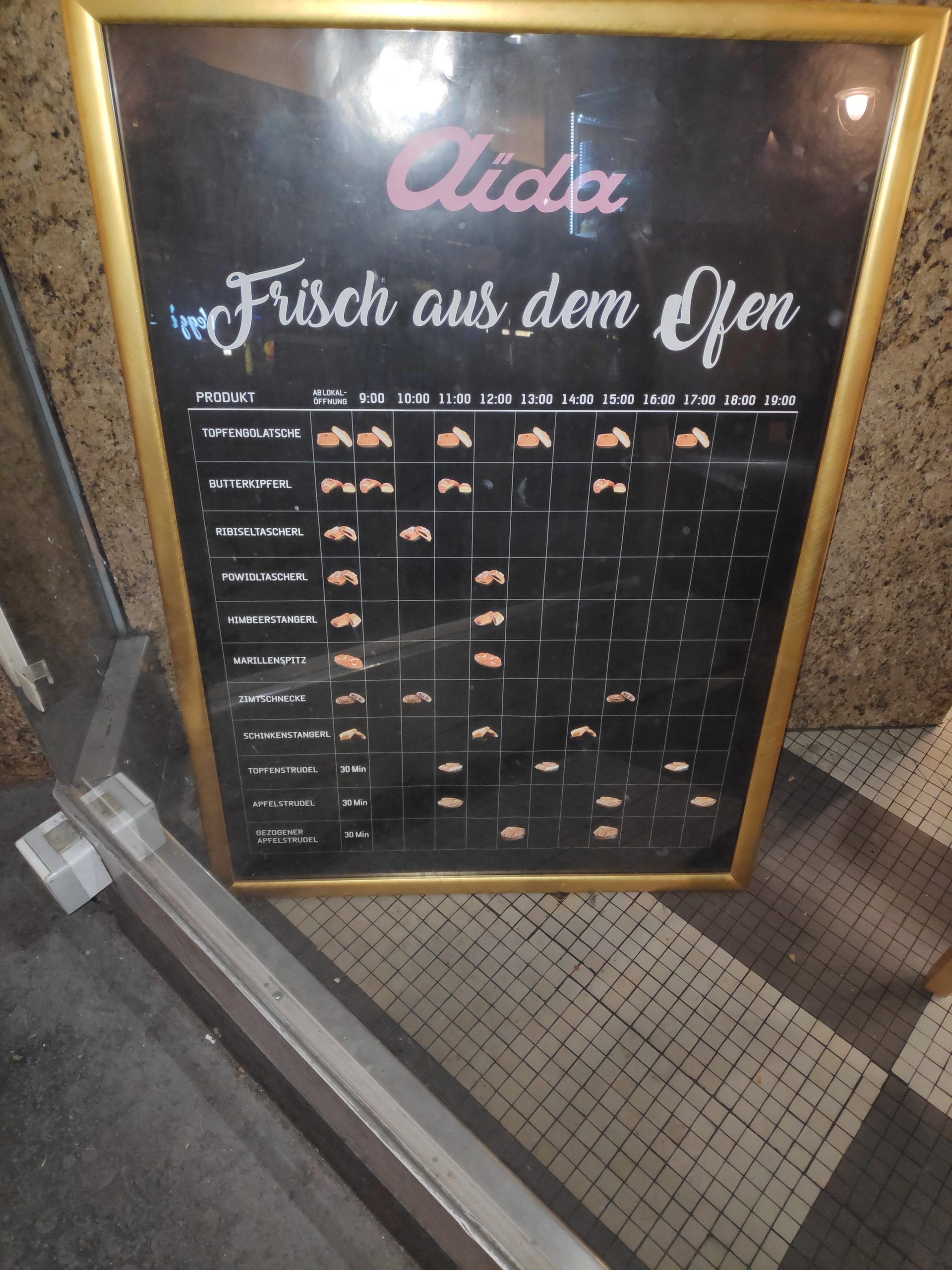 A timetable in front of a bakery that tells you when they bake fresh pasteries.